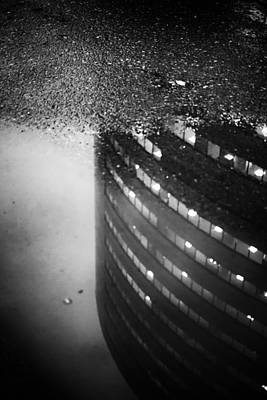 Photograph - Building Reflection In A Puddle Of Water by John Williams