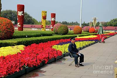 Photograph - Chinese Security Guard Sits In Front Of Flower Display Beijing China by Imran Ahmed