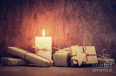 Burned Photograph - Chistmas Presents, Gifts With A Candle Glowing On Wooden Wall Background. by Michal Bednarek