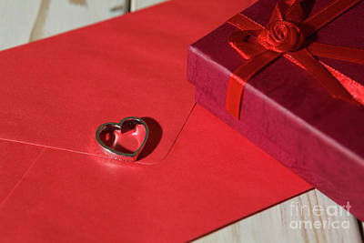 Sterling Silver Photograph - Closeup Of A Silver Heart Pendant On A Red Envelope And Gift Box by Luigi Morbidelli