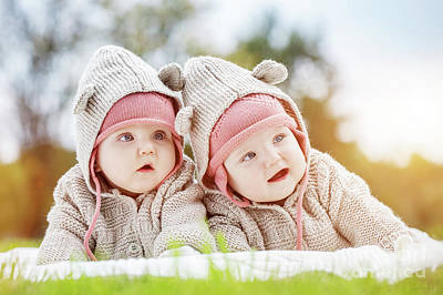 People Photograph - Cute Baby Twins Lying Together In A Park Wearing Funny Cozy Sweaters. by Michal Bednarek