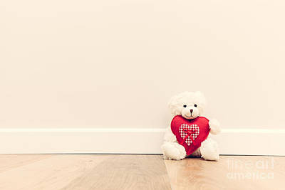 Bear Photograph - Cute Teddy Bear With Big Red Plush Heart. Sitting On Wooden Floor Against White Wall by Michal Bednarek