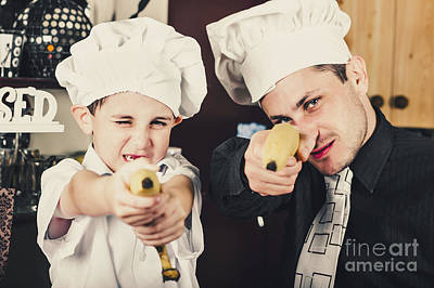 Dad And Son Cooks Shooting With Bananas In Kitchen Print by Jorgo Photography - Wall Art Gallery