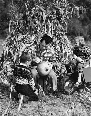 Jack O Lanterns Jackolantern Photograph - Dad Carves Pumpkin As Kids Watch by H. Armstrong Roberts/ClassicStock