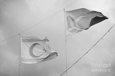 flags of turkey and TRNC turkish republic of northern cyprus flying in the sky above nicosia cyprus Art Print by Joe Fox