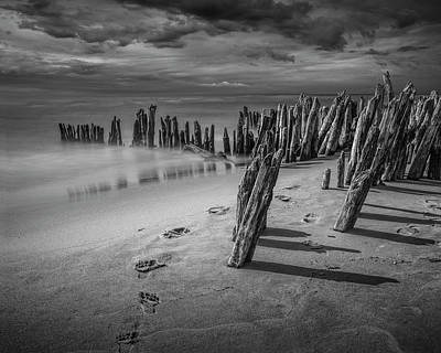 Photograph - Footprints And Pilings On The Beach In Black And White by Randall Nyhof