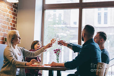 Photograph - Four Friends Sitting Together With Glasses Of Champagne. by Michal Bednarek