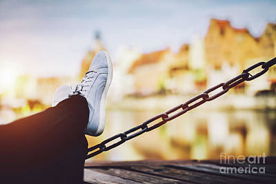 Photograph - Girl's Legs Leaning On A Chain, A River And Old Buildings In Background by Michal Bednarek