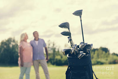Photograph - Golf Bag Standing On A Grass Field, People In The Background by Michal Bednarek