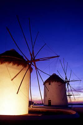 Greece. Mykonos Town. Illuminated Windmills At Dusk. Art Print by Steve Outram