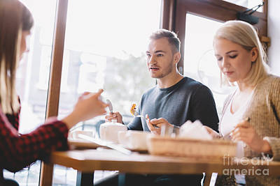 Photograph - Group Of Friends Eating Out In A Restaurant by Michal Bednarek