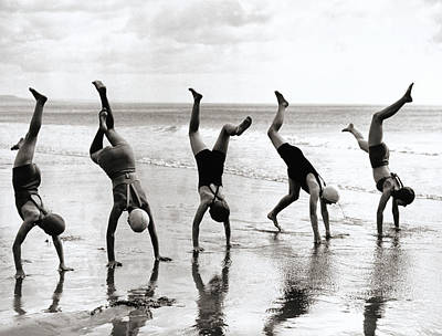 One Piece Swimsuit Photograph - Group Of People Doing Handstands On Beach (b&w) by Hulton Archive