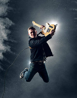 Rock And Roll Royalty-Free and Rights-Managed Images - Guitarist jumping high by Johan Swanepoel