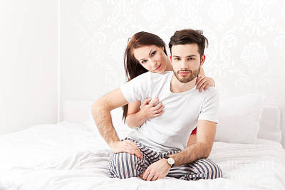 Lifestyle Photograph - Happy Couple Sits With Sleeping Garment On Bed by Wolfgang Steiner
