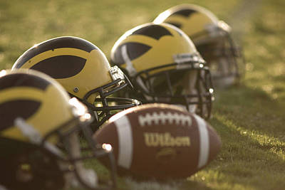 Photograph - Helmets And A Football On The Field At Dawn by Michigan Helmet