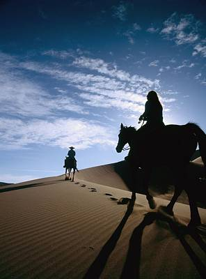 Horseback Riders In Silhouette On Sand Print by Axiom Photographic