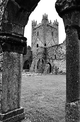 Ireland Photograph - Jerpoint Abbey Tower Ruins Between Arched Cloister Columns County Kilkenny Ireland Black And White by Shawn O'Brien