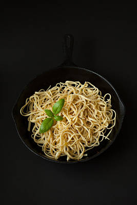 Linguine In A Cast Iron Pan With Basil On Black Background Print by Erin Cadigan