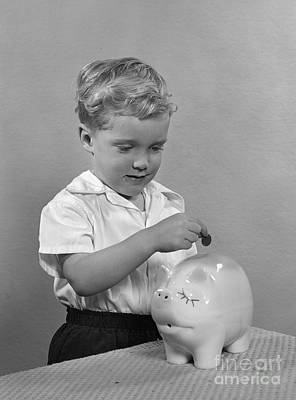 Little Boy Putting Coin Into Piggy Art Print by H. Armstrong Roberts/ClassicStock