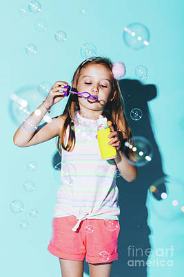 Photograph - Little Girl Blowing Soap Bubbles On A Blue Background. by Michal Bednarek