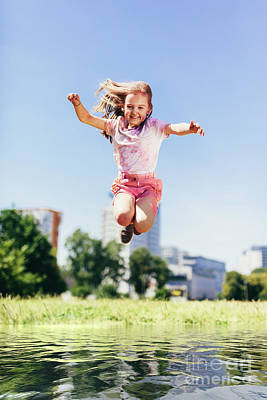Photograph - Little Girl Jumping High Above Big Puddle Of Water. by Michal Bednarek