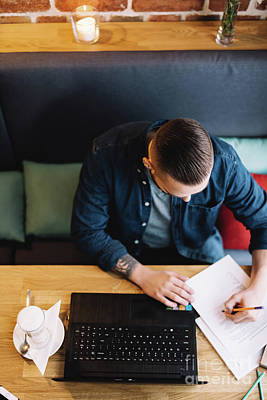 Photograph - Man Doing Paperwork In A Cafe. by Michal Bednarek