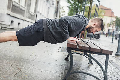 Photograph - Man Doing Push-ups On A Bench. by Michal Bednarek