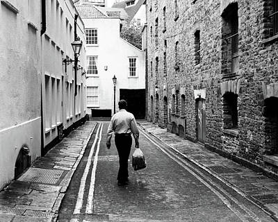 Photograph - Man Walking With Shopping Bag Down Narrow English Street by Jacek Wojnarowski