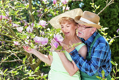 Retirement Photograph - Mature Couple In Sunhats Embracing In Garden, Hugging And Smiling. by Michal Bednarek