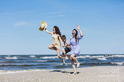 Photograph - Mother And Her Children Jumping High On The Beach. by Michal Bednarek