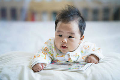 Photograph - Newborn Baby Play Smart Phone On The Bed by Anek Suwannaphoom