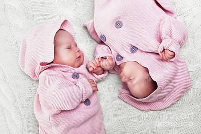 Little Photograph - Newborn Twins Sisters Sleeping On White Fur, Wearing Pink Sweaters by Michal Bednarek