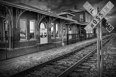 Randall Nyhof Royalty Free Images - Old Train Station with Crossing Sign in Black and White Royalty-Free Image by Randall Nyhof
