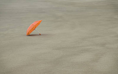 Photograph - Orange Umbrella In The Sand by Don Schwartz