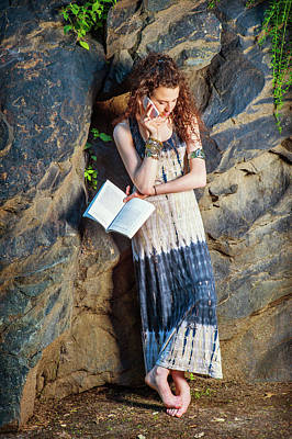Photograph - oung American Woman reading book, talking on cell phone, traveli by Alexander Image