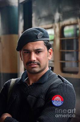 Photograph - Pashtun Railway Police Officer Stands Guard At Train Station Peshawar Pakistan by Imran Ahmed