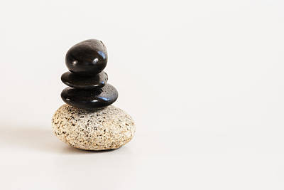 Balancing Act Photograph - Pebbles Stacked On A White Background by Vishwanath Bhat