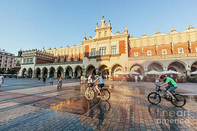 Photograph - People Cycling On The Main Market Square Of Cracow, Poland by Michal Bednarek
