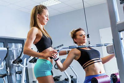 Photograph - Personal Trainer Assists Client While Workout. by Michal Bednarek