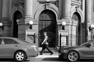 Photograph - Philadelphia Man Walking Between Cars - Black And White by Matt Harang