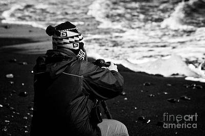 Bergy-bit Photograph - photographer taking photos of Ice washed up on black sand beach at jokulsarlon iceland by Joe Fox
