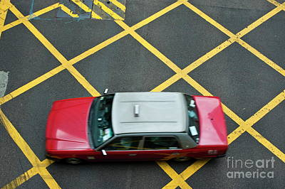 Red Taxi Cab Driving Over Yellow Lines In Hong Kong Art Print by Sami Sarkis