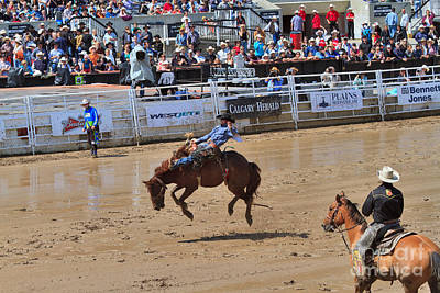 Bronc Photograph - Saddle Bronc Riding Event At The Calgary Stampede by Louise Heusinkveld