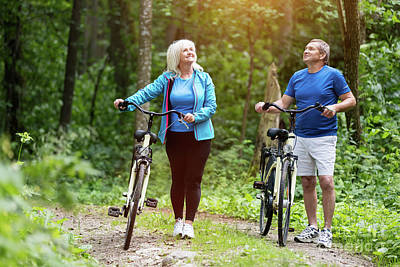 Photograph - Senior Couple Enjoying Their Walk In The Forest. by Michal Bednarek