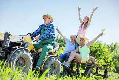 Photograph - Senior Man Taking Family For Ride On Tractor by Michal Bednarek