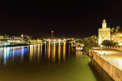 Photograph - Seville Night Magic - Torre Del Oro And Guadalquivir River In Bright Gold by Georgia Mizuleva