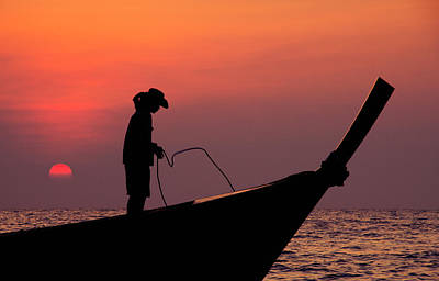 A Summer Evening Photograph - Silhouette Of A Young Man With Cowboy Hat In A Wooden, Longtail Thai Boat At Sunset by Srdjan Kirtic