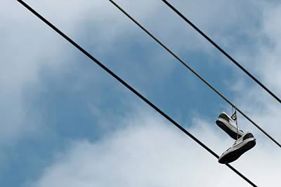 Zen Garden - Sneakers hanging from wire by Emma Grimberg