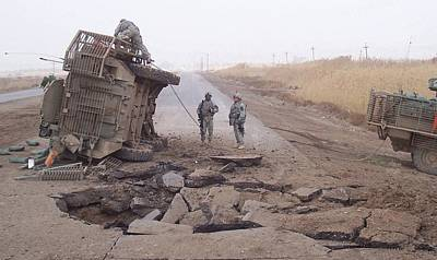 Improvised Explosive Device Photograph - Stryker Vehicle Lies On Its Side by Everett