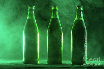 Photograph - Three Green Beer Bottles On A Dusty Background. by Michal Bednarek
